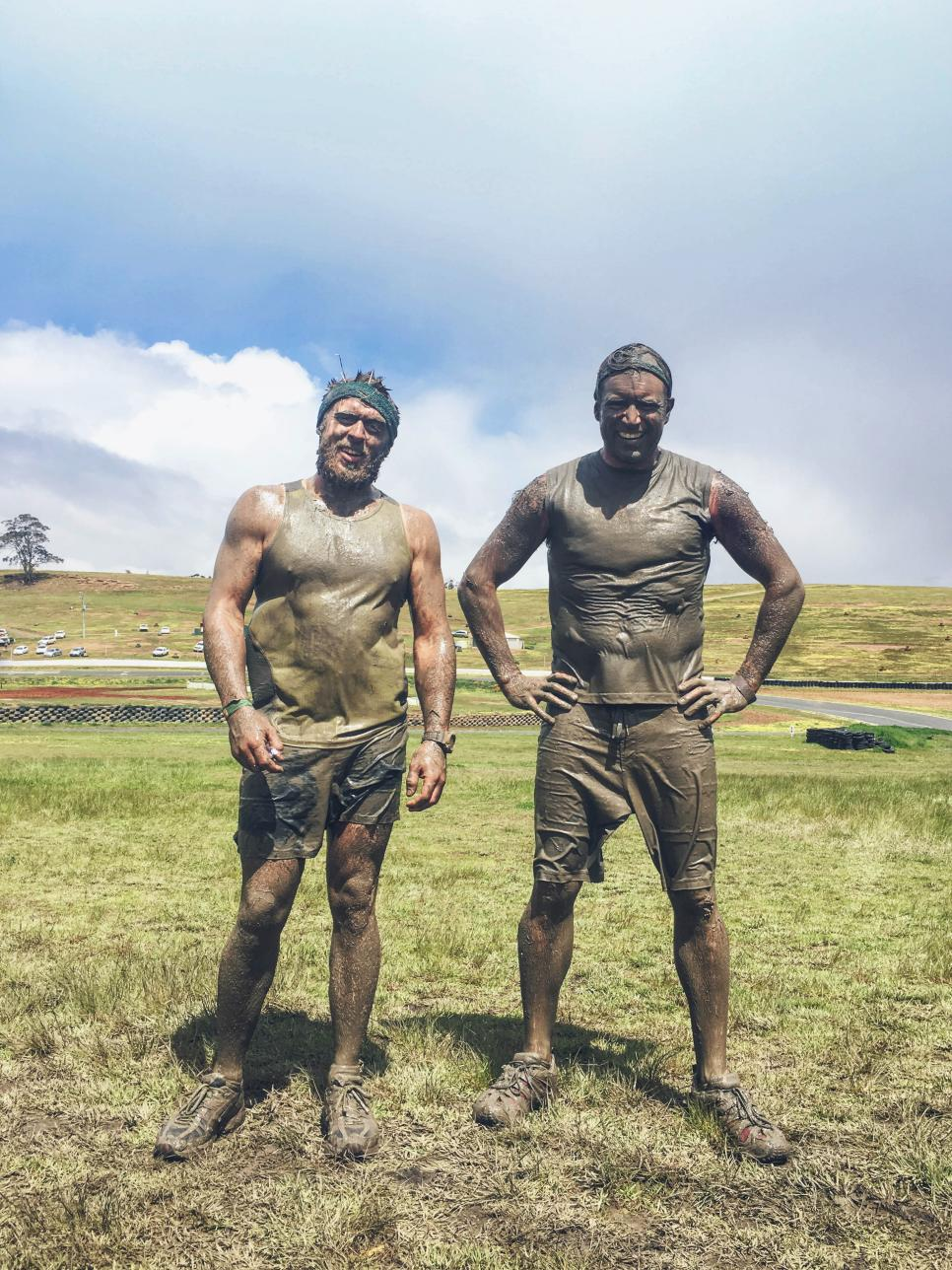 Two happy men standing together after completing a mud run challenge