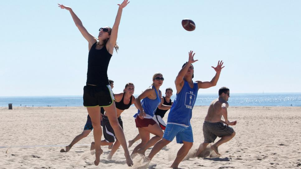 Megan Macdonald jumps to block a pass during a co-ed touch football game in Huntington Beach.