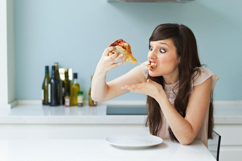 Portrait of woman eating pizza