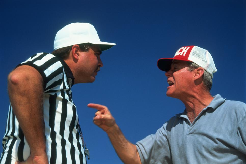 Referee and coach arguing, close-up