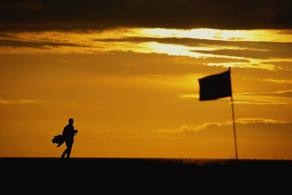 Golfer carrying clubs, walking across green at sunset, silhouette