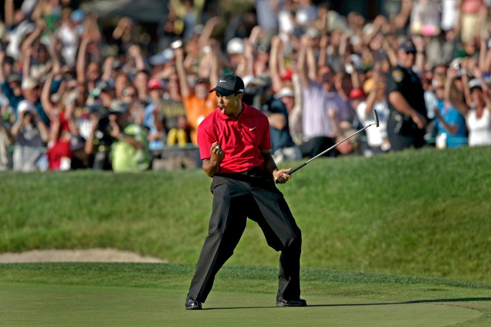 Tiger Woods celebrates on the eighteenth green after sinking a putt for a birdie and to force a pla
