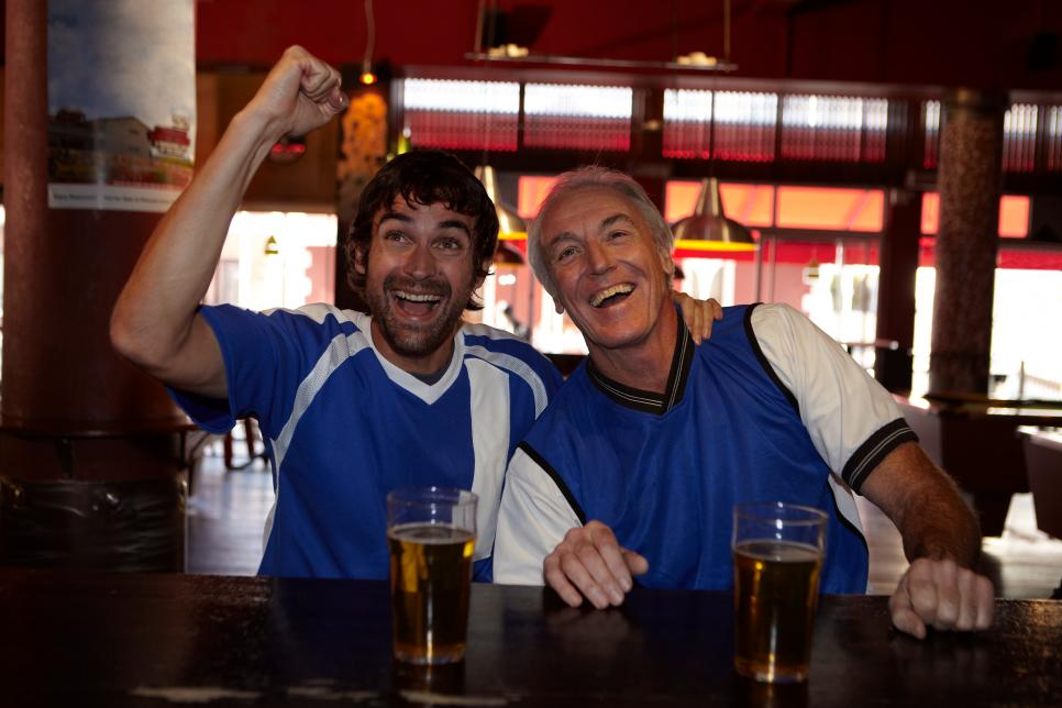 Father and son celebrating in bar
