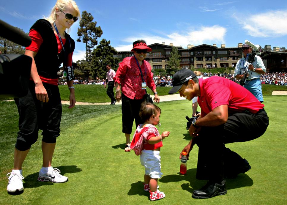Golfer Tiger Woods, right, greets his daughter Sam, center,