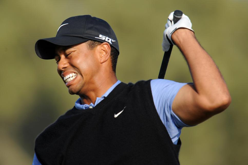 Tiger Woods winces in pain as he follows