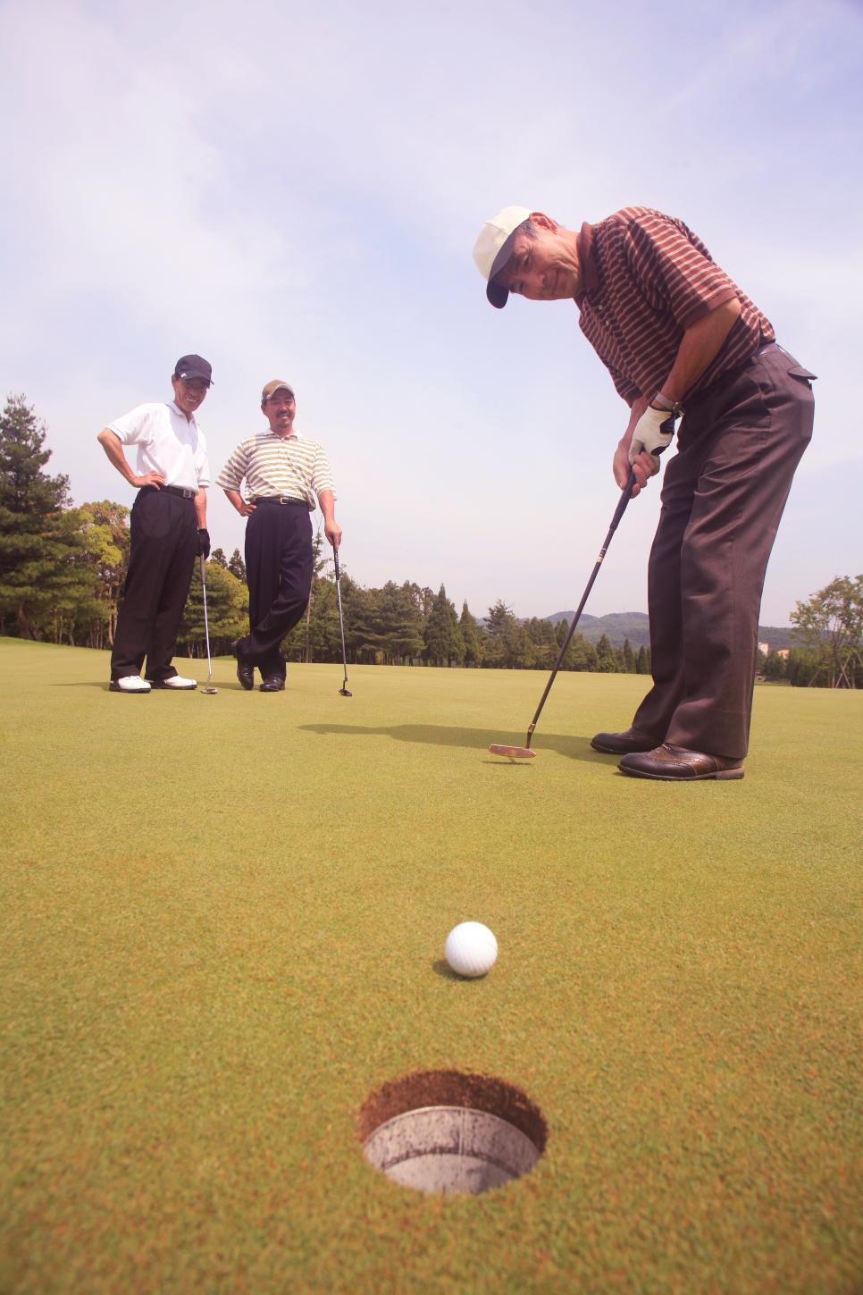 Three mature men playing golf (focus on hole in foreground)