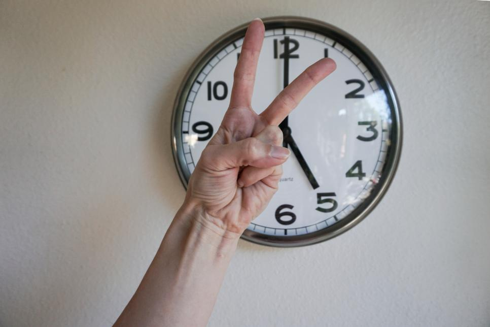Hand showing victory sign in front of a clock, at five p.m.