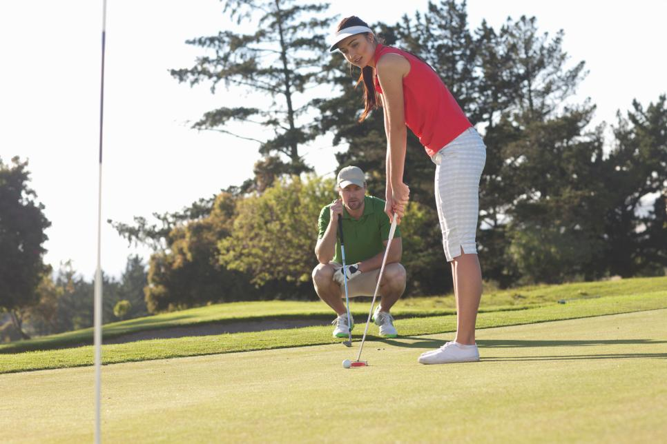 Young female golfer on golf course with trainer