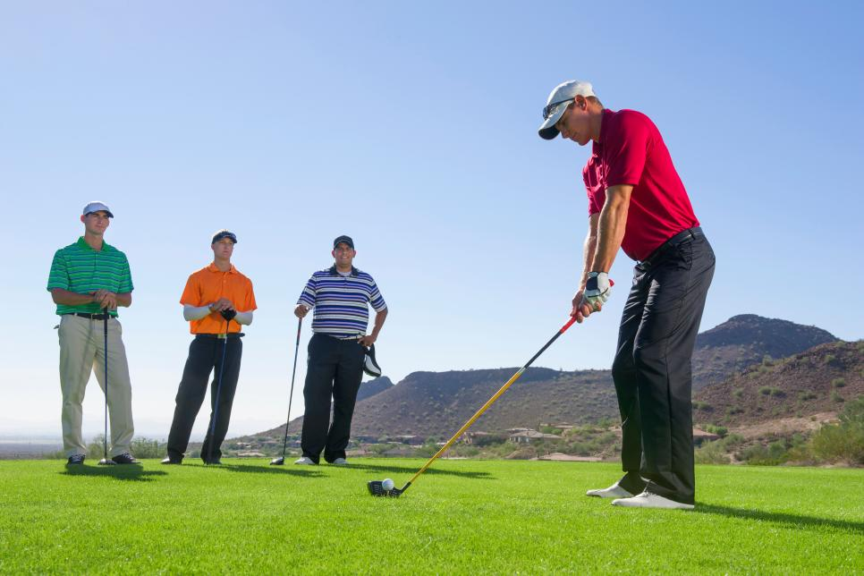 Men playing golf on course