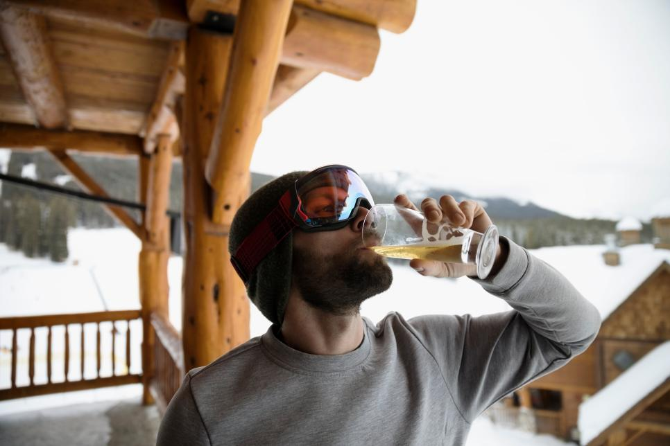 Male skier in ski goggles enjoying apres-ski, drinking beer on snowy ski resort lodge balcony