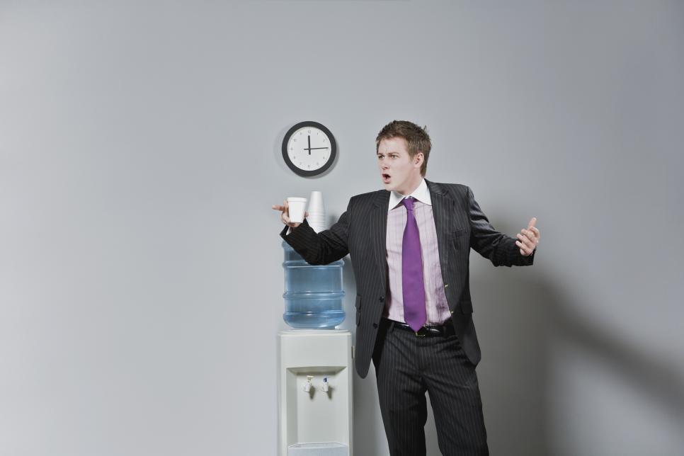 Businessman looking surprised near a water cooler