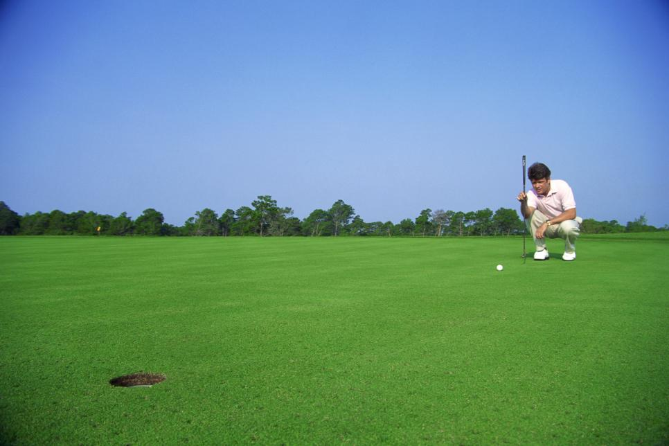 Man squatting to line up his putt on a golf course