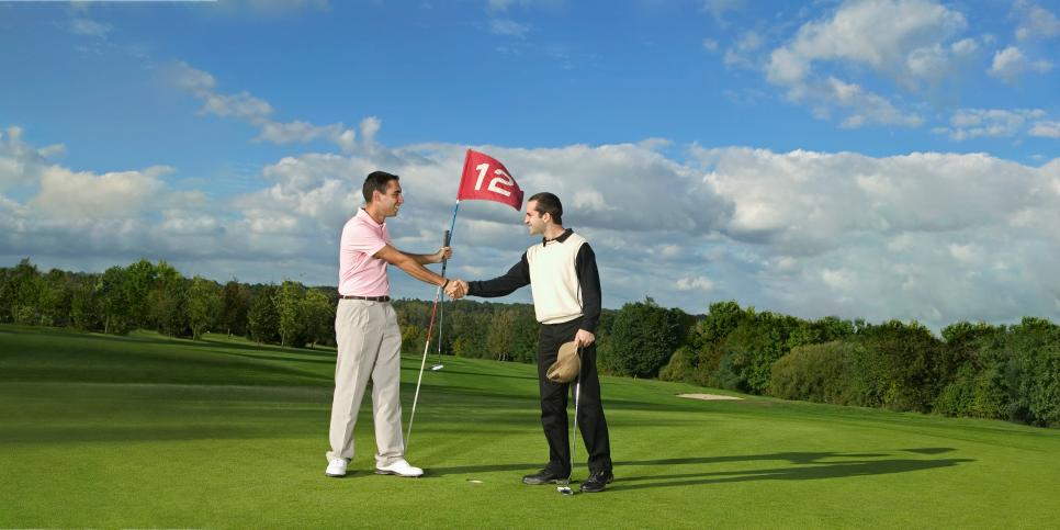 Two male golfers, standing on green shaking hands