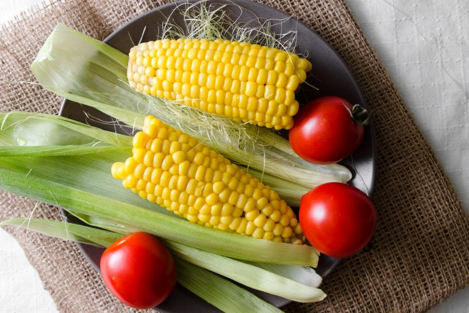 Boiled corn and raw tomatoes in a plate. Tasty and healthy vegetarian meal