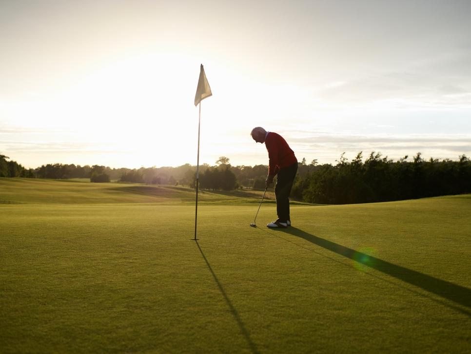 Male golfer preparing to putt ball.