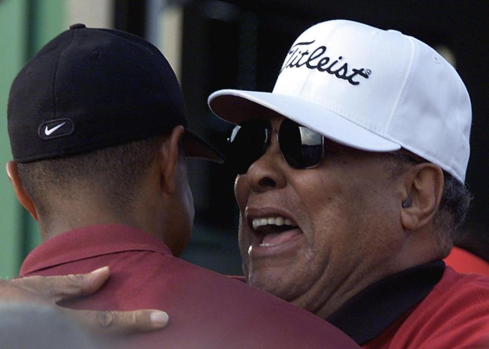 Tiger Woods of the US (L) is hugged by his father